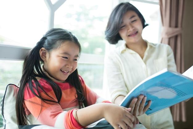 Crianças asiáticas lendo livro com a mãe na sala de estar.
