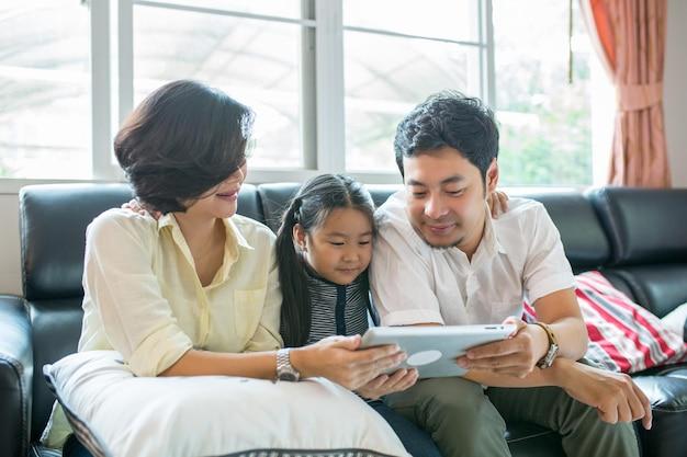 Crianças asiáticas lendo livro na sala de estar.