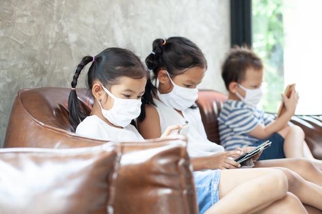 Crianças asiáticas menino e meninas vestindo máscara de proteção jogando no smartphone juntos em quarentena em casa do coronavírus covid-19 e poluição do ar pm2.5.
