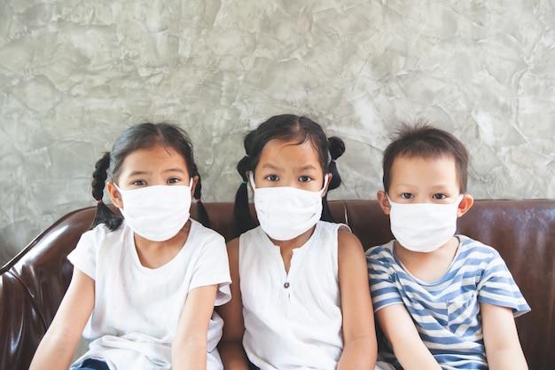 Crianças asiáticas meninos e meninas que usam máscara de proteção ficam em casa em quarentena contra o coronavírus covid-19 e a poluição do ar pm2.5.