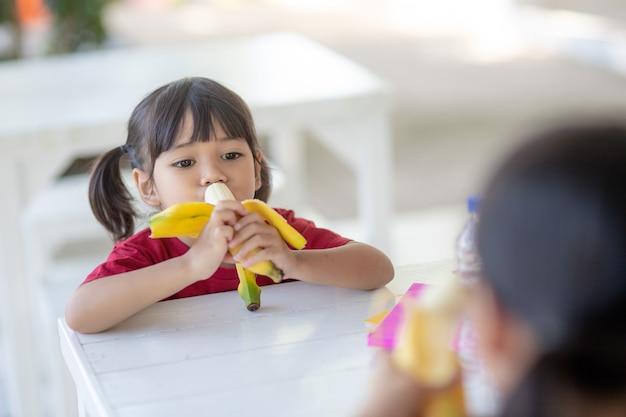 Crianças asiáticas na cantina, almoçando ou tomando café da manhã, estão se divertindo