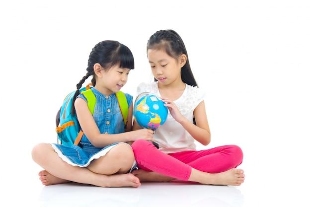 Crianças asiáticas, olhando o globo