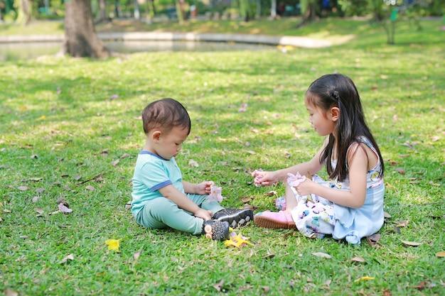 Crianças asiáticas que jogam junto no jardim verde do gramado. irmã brincar com seu irmão mais novo ao ar livre.