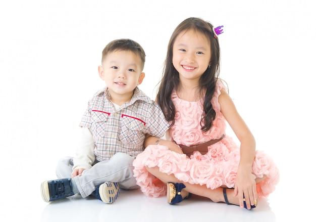 Crianças asiáticas sentado no chão