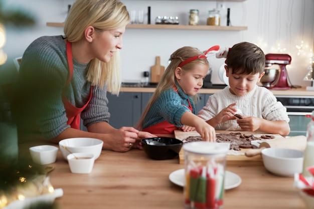 Crianças assando biscoitos de gengibre em cozinha doméstica