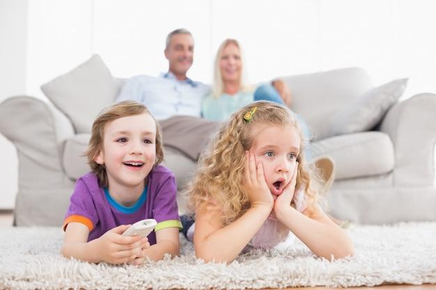 Crianças assistindo tv enquanto pais sentados no sofá