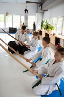 Crianças atentas e sérias ouvindo atentamente seu professor de aikido
