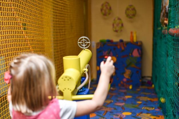Crianças atiram em alvos com uma arma de brinquedo