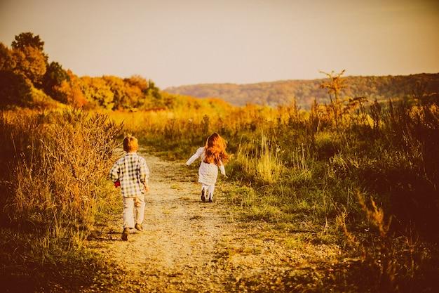 Crianças atravessam um campo de outono