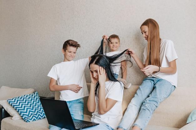 Crianças barulhentas distraem as mães do trabalho no computador e mãe irritada segura a cabeça