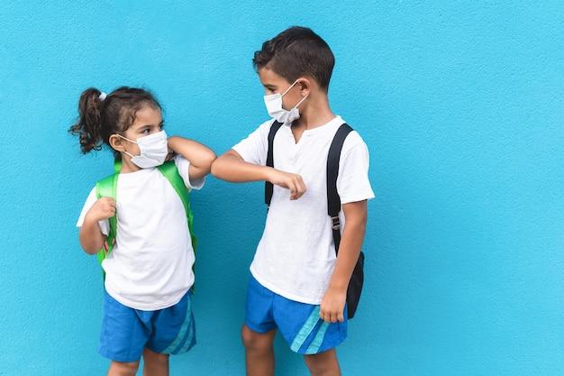 Crianças batem com os cotovelos em vez de cumprimentá-los com um abraço - evite a propagação do coronavírus, da distância social e do conceito de amizade concentre-se no rosto de criança do sexo masculino