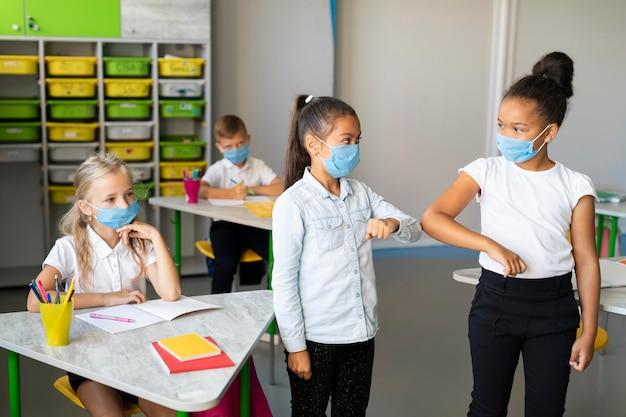 Crianças batendo o cotovelo na sala de aula