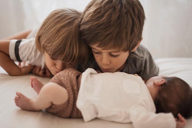 Crianças beijando seu irmãozinho