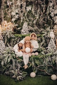 Crianças bonitas brancas posam para a câmera em uma bela decoração de natal e sorriem