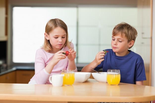 Crianças bonitas comendo morangos para o café da manhã