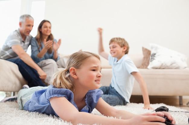 Crianças bonitas jogando videogames com os pais nas costas