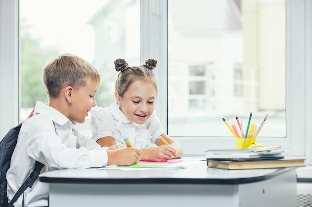 Crianças bonitas são alunos juntos em uma sala de aula na escola recebem educação felizes