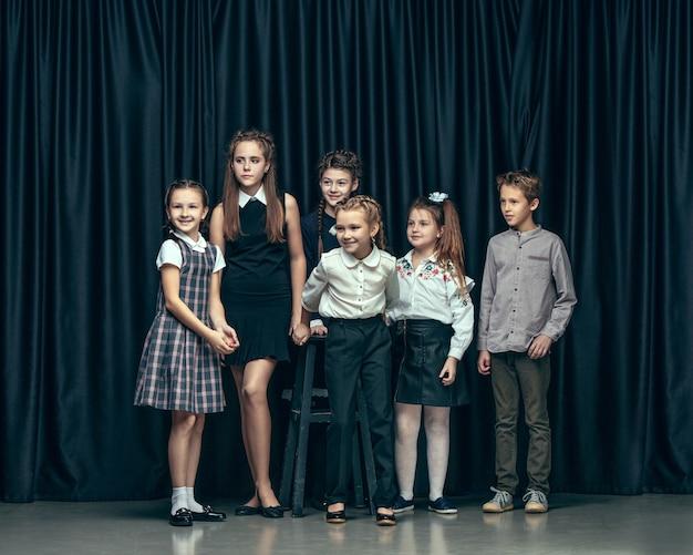Crianças bonitos e elegantes em fundo escuro do estúdio. as lindas meninas adolescentes e meninos juntos