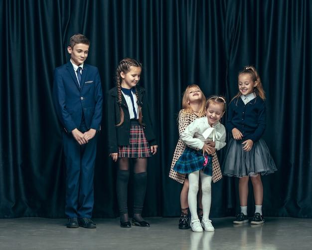 Crianças bonitos e elegantes no estúdio escuro. as lindas meninas adolescentes e meninos juntos
