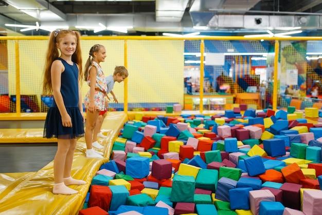 Crianças bonitos pulando na cama elástica de crianças, playground no centro de entretenimento.