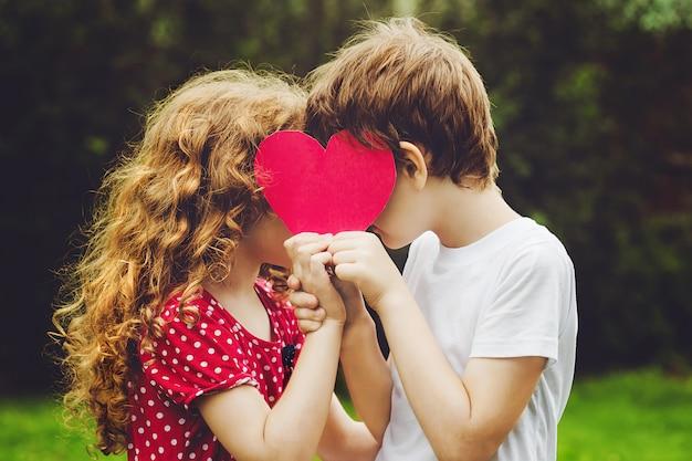 Crianças bonitos que guardam a forma vermelha do coração no parque do verão.