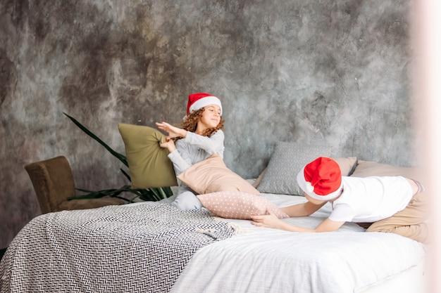 Crianças bonitos tween em chapéus de papai noel e pijama brincando na cama com travesseiro, tempo de manhã de natal, festa de crianças