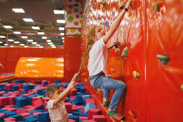 Crianças brigam na parede de escalada do centro de entretenimento. férias de meninos e meninas nos feriados, felicidade infantil, crianças felizes no parquinho