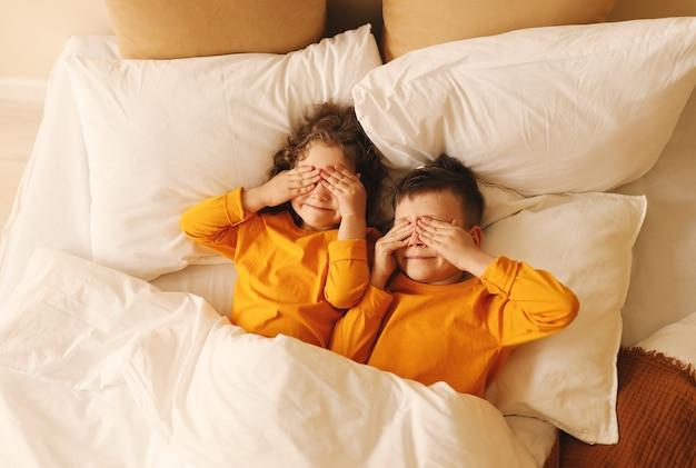 Crianças brincalhonas de pijama amarelo deitam-se na cama com os olhos fechados