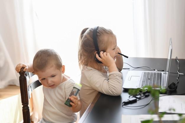 Crianças brincam com o computador dos pais