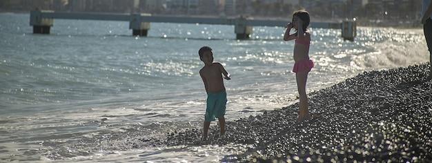 Crianças brincam na praia, imagem de banner com espaço de cópia