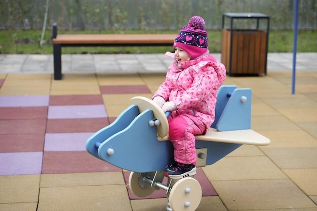 Crianças brincam no parquinho, meninos e meninas felizes e rindo, se divertindo balançando e escalando ao ar livre