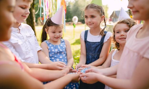 Crianças brincando ao ar livre na festa de aniversário no jardim no verão, o conceito de celebração.