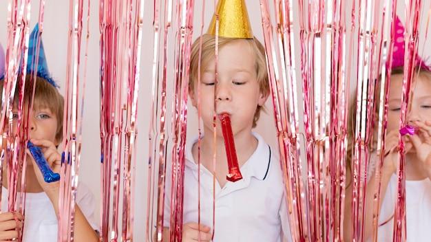 Crianças brincando com apitos de festa