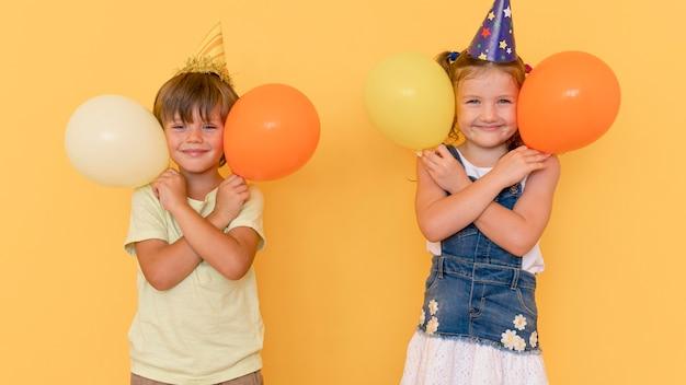 Crianças brincando com balões de frente