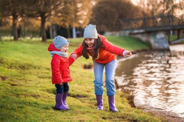Crianças brincando com barquinhos de papel no lago