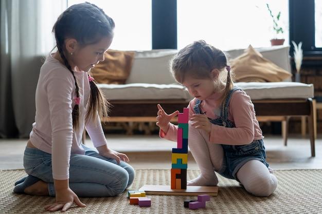 Crianças brincando com blocos de madeira no chão do quarto.
