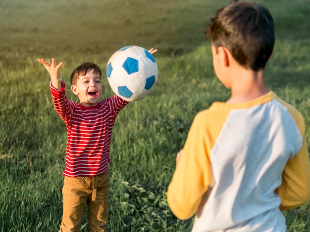 Crianças brincando com bola ao ar livre