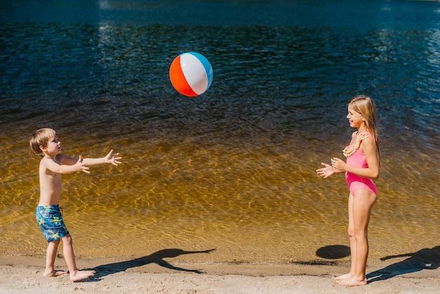 Crianças brincando com bola de praia em pé perto do mar