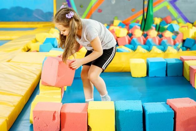 Crianças brincando com cubos macios na piscina seca no play center. playground com blocos de espuma no clube trampolim