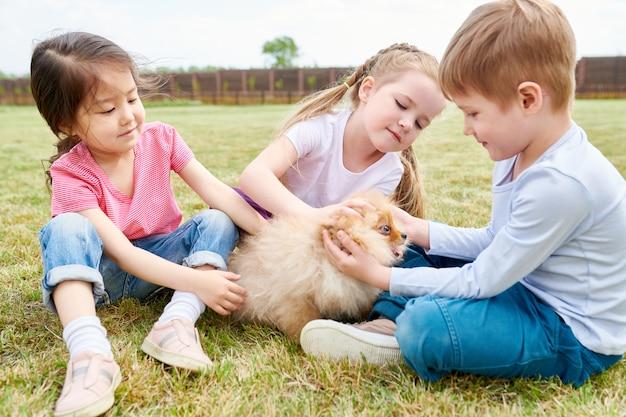 Crianças brincando com filhote de cachorro bonito
