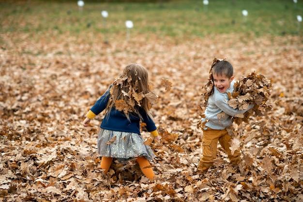 Crianças brincando com folhas de outono