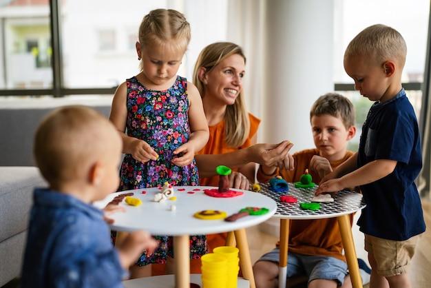 Crianças brincando com massinha. a professora ou a mãe brincam com as crianças. pessoas, conceito de criatividade infantil