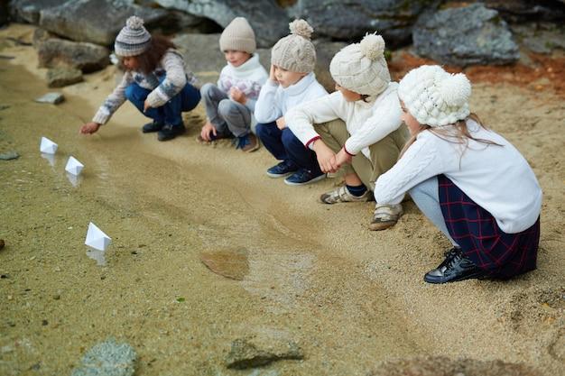 Crianças brincando com navios de papel no lago