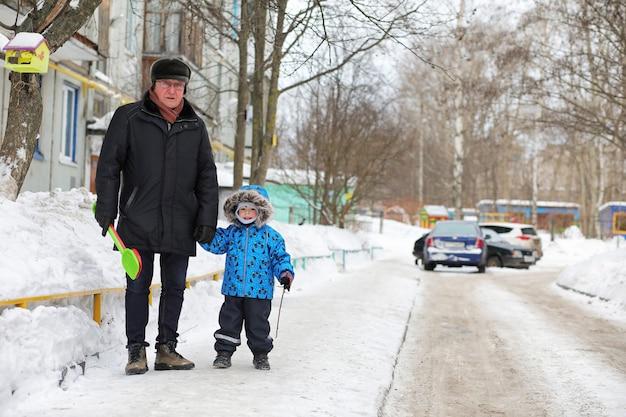 Crianças brincando com neve no inverno no quintal da cidade Foto Premium