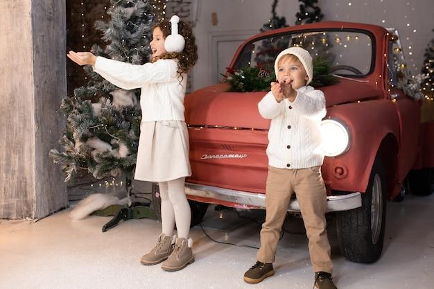Crianças brincando com neve perto de um carro vermelho e uma árvore e luzes de natal