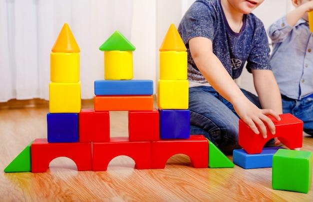 Crianças brincando com o construtor no chão em casa. crianças em idade pré-escolar se divertindo. creche, desenvolvimento infantil. tijolos de plástico coloridos no chão. mãos fechadas