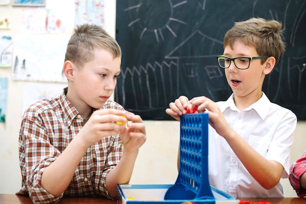Crianças brincando com o jogo de lógica