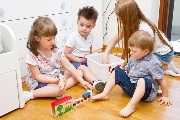 Crianças brincando com o trem de madeira na sala