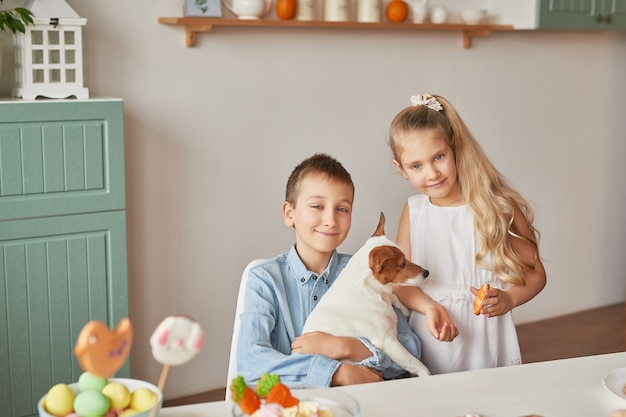 Crianças brincando com seu cachorro em uma mesa decorada com páscoa