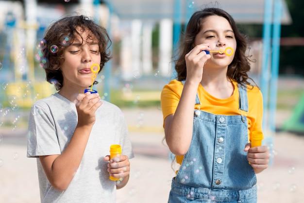 Crianças brincando com soprador de bolhas